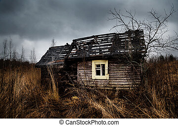 Ruined Old haunted house on the empty field with dramatic blue sky