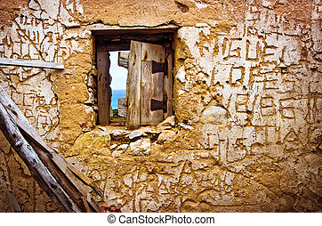 Detail of a broken window in a wall with carved sayings inside a ruined house