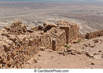 Ruined wall of ancient fortress on the mountain in the desert