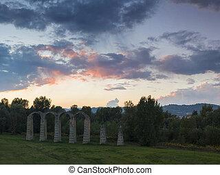Ruins of an ancient roman aqueduct at sunset