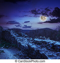 ruins of an old castle in the mountains at night