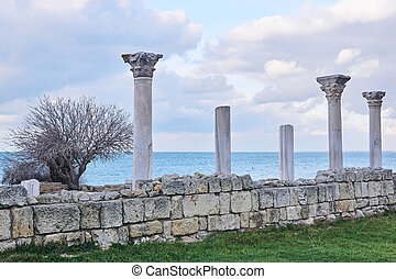 ruins of antique greek temple with columns on the seashore