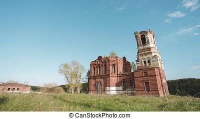 Ruins of one abandoned church from red bricks in Russia. Video. Outdoor on field on blue summer sky background. Beautiful scenic view of ancient Buddhist Temple at the background of field.