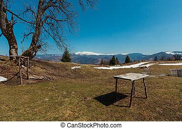 Ruins on animal husbandry farmland on early spring Carpathian mountains plateau top.