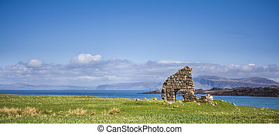 Landscape displaying ruins of an old chapel on the Scottish Isle of Iona, with the sea and the Isle of Mull in the background.