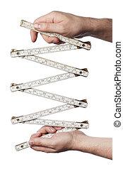 Ruler - Man holding an old folding carpenter\'s ruler