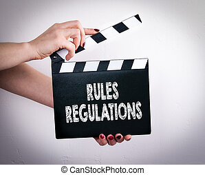 Rules And Regulations. Female hands holding movie clapper