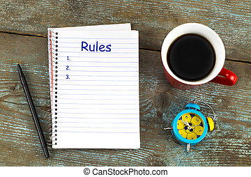 Rules list with notebook, cup of coffee on wooden desk. Top view