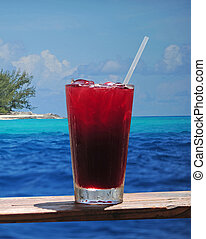 Rum punch or fruity drink in a tropical paradise with a turquoise ocean and clear blue water