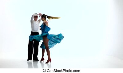 Rumba dancing couple of professional elegant dancers,slow motion. White studio
