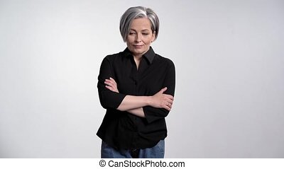 Ruminating adult woman with gray hair showing facial ...