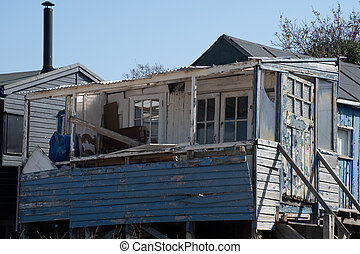 Run down blue large wooden shack by coast
