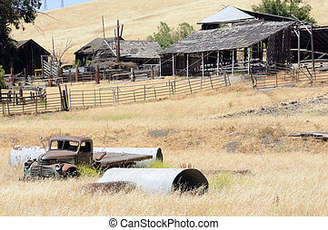 Run down farm with old truck in field