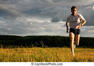Photo of athlete in sportswear running outdoor
