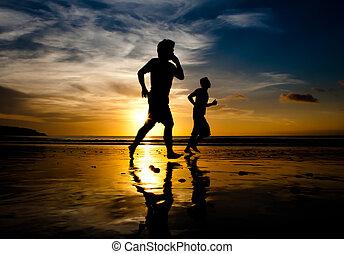Two men running on Jimbaran beach at sunset in Bali