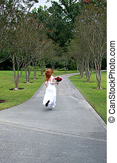 A beautiful redheaded bride running away, or rushing late