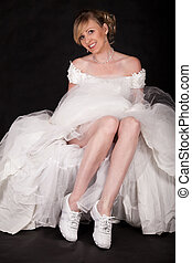 Full body of an attractive blond woman lifting up white wedding gown with wide flowing skirt to show white running shoes on underneath smiling
