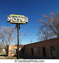 Rundown motel building with blue sky in background.