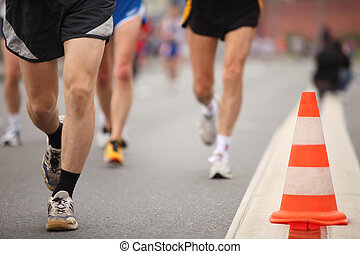 Runing man's legs in sport shorts and jogging shoes near color cone on asphalt