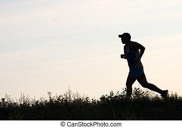 runner against sky - silhouette of running man on the...