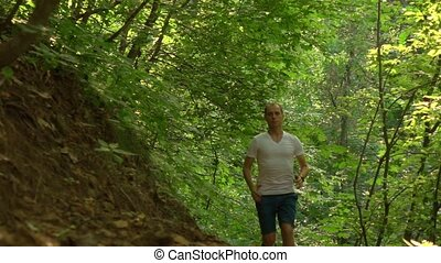 Runner approaching camera in the forest. Super slow motion long shot