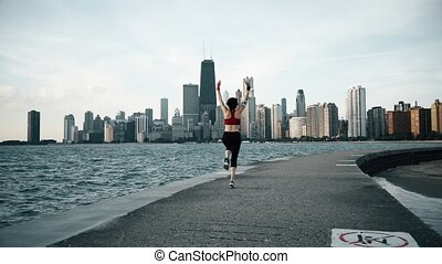 Runner athlete doing exersises at seaside with skyscrapers on the background. Woman fitness silhouette sunrise workout.