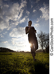 Runner athlete feet running on country side. woman fitness silhouette sunrise jog workout wellness concept.