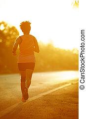 Runner athlete feet running on road. woman fitness silhouette sunrise jog workout wellness concept