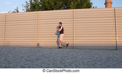 Runner - athlete man running training outdoors exercising on mountain road. Slow motion