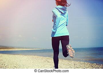 Runner athlete running on stone beach . woman fitness jogging workout wellness concept.