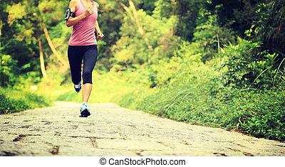 Runner athlete running on forest trail. woman fitness...