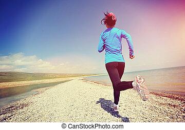 Runner athlete running on stone beach , woman fitness...