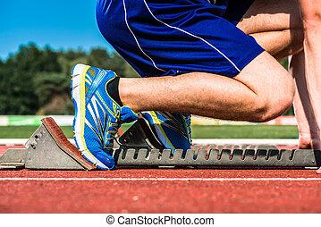 Runner before start signal on starting block of sprint track...