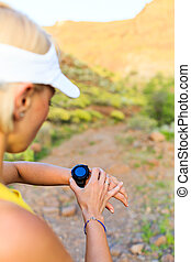Woman runner checking the elevation on sports watch, smartwatch with altimeter app in summer mountains. Young girl training and running on mountain trail in the morning.