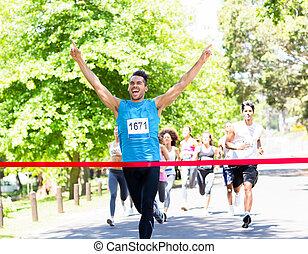 Runner crossing the finshline - Excited male runner crossing...