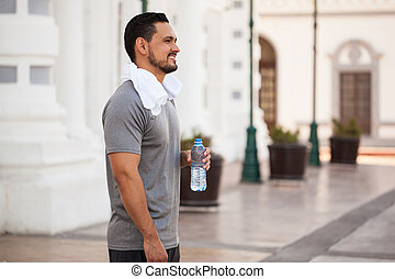 Runner exercising and taking a water break - Profile view of...