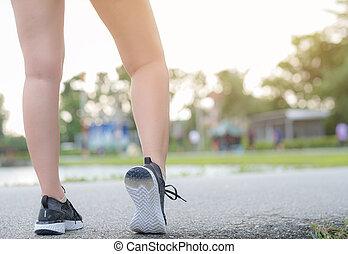 Runner feet running on road closeup leg on shoe. woman fitness sunrise jog workout welness concept.