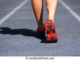 Runner feet running on road closeup on shoe. Woman fitness jog workout welness concept.