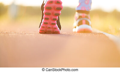 Runner feet running on road closeup on shoe. woman fitness sunrise jog