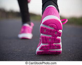 Runner feet running on road. Shoe close-up.