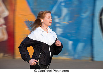 Runner girl on jogging practice beside graffiti wall