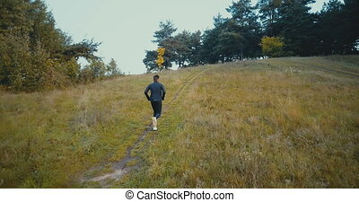 Runner going uphill on a small path to forest. Drone back...