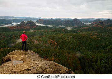 Runner in pink jacket and light black trousers. Short ginger hair man in his target. Tired sportsman take a rest on thepath in rocks.