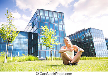 Runner in the city resting in front of glass buildings. -...