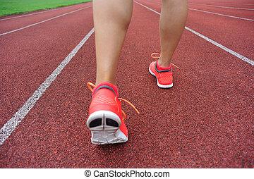 runner legs on red running track in stadium