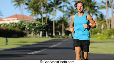 Runner looking at his heart rate monitor, activity tracker smartwatch. Active athlete man looking at his smart watch using app on watch while running outside on road. Male athlete.