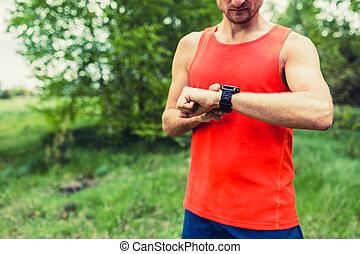Runner looking at sport smart gps watch - Runner on mountain...