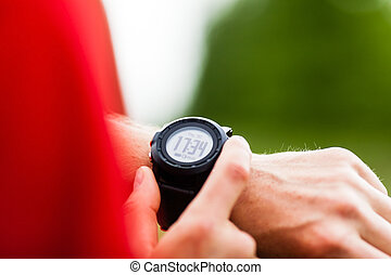 Runner looking at sport watch - Runner on mountain trail ...