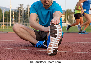 Runner making stretching on the track