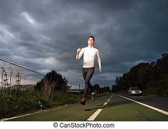 Runner man in the road at night outdoors